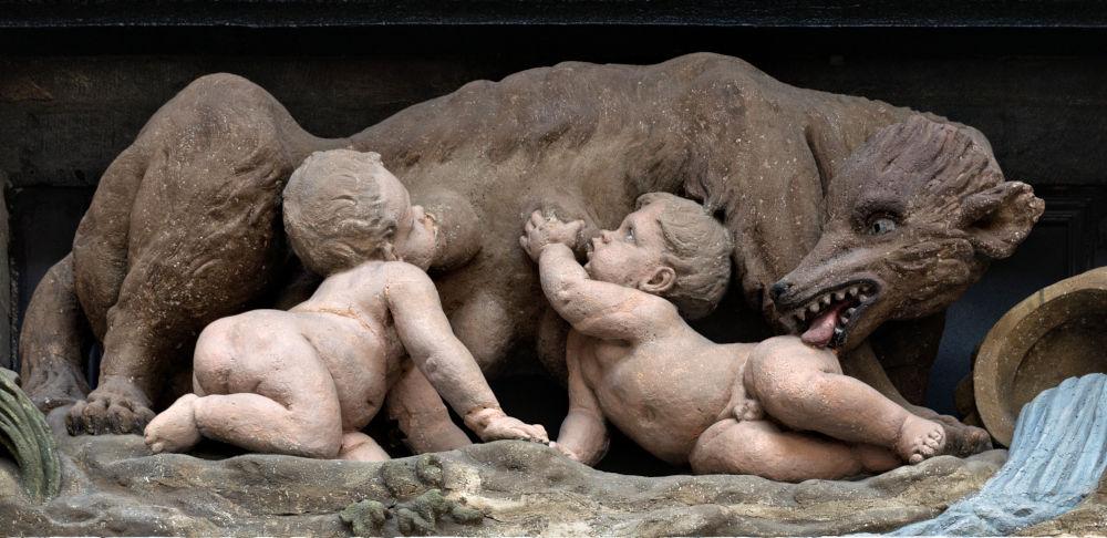Wölfliche Kinderpflege: Romulus und Remus (Maison de la Louve in Brüssel, Fotografie: Trougnouf, bearbeitet; Creative-Commons-Lizenz https://creativecommons.org/licenses/by/4.0/deed.de)